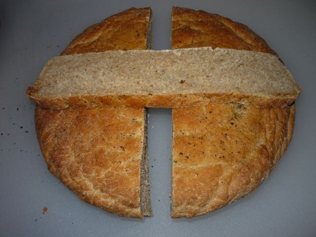 Bread with a slice cut out, laying across the two halves, showing a thin, light crust and normal crumb texture.