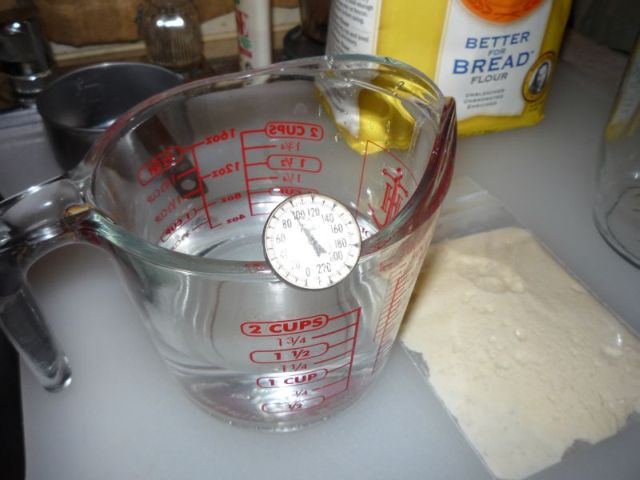 Measuring cup with water and thermometer.