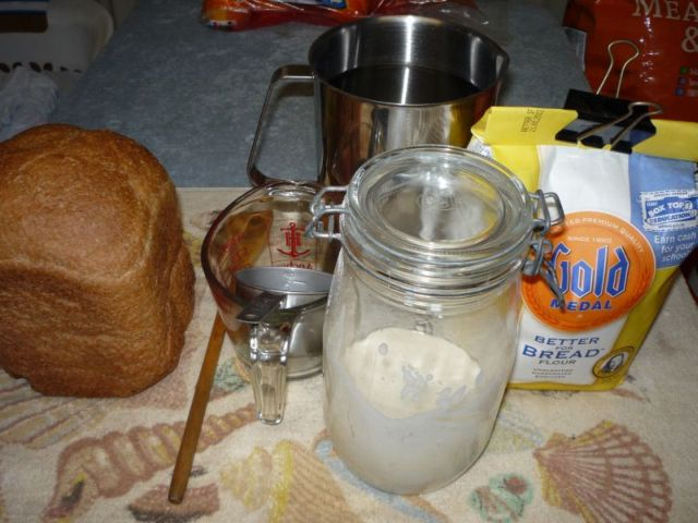 Jar with starter, water, flour, and utensils.