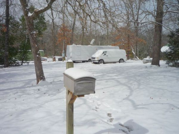 Snow-covered mail box and yard.