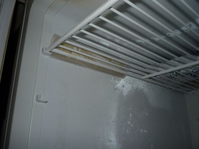 Baggie tucked between wall of freezer and grille.