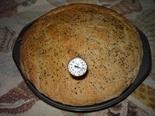 Top of baked round bread, with stem thermometer inserted, reading 183.