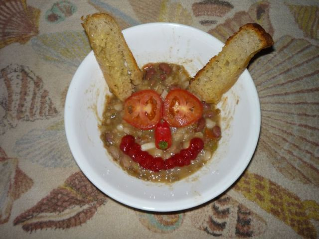 Soup in a large bowl, with vegetables arranged into a funny face, with two breads as rabbit ears.